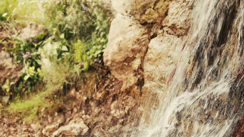 A small waterfall splashing in the mountains. Water. Spay. Nature. Greenery Footage