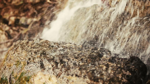 A small waterfall splashing on rock in the mountains. Water. Spay. Nature Footage