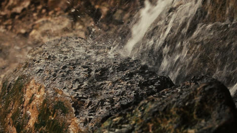 A small waterfall splashing on rock in the mountains. Spay. Nature. Wetting Footage