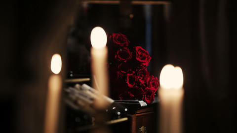White candles burning. Fire. Bouquet of red roses on background. Flame Footage