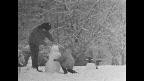 children together with their parents building a snowman ( 16mm film reel) retro Footage
