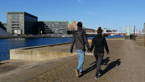 Couple walking hand in hand along the harbor Footage