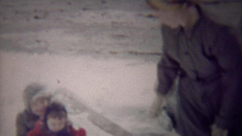 1954: Mom loads happy kids winter snow sled pull down sidewalk Footage