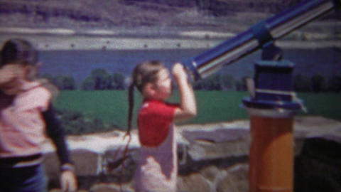 1954: Brother lets kid sister look telescope looking glass attraction Footage