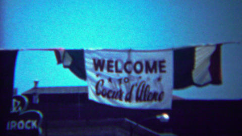 1954: Welcome Coeur D' Alene flag sign hanging above main street Footage