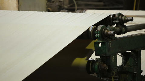 paper rolling through an automated paper bag making and folding assembly machine Live Action