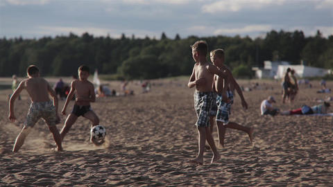 Friends Playing Football On Beach stock footage