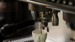 Coffee maker pours hot coffee into white cup. Fail coffee flows past the cup Live Action
