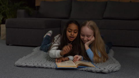 Happy multiracial kids reading fairytales at home Footage