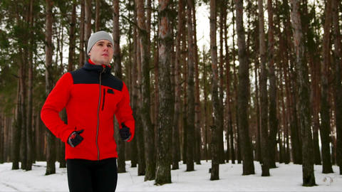 A young sporty man in a red jacket spends his training in the fresh air running Live Action
