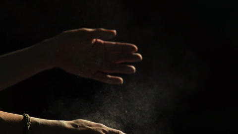 Close-up on a black background hands of a professional climber in magnesia Live Action