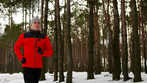 A young sporty man in a red jacket spends his training in the fresh air running Footage