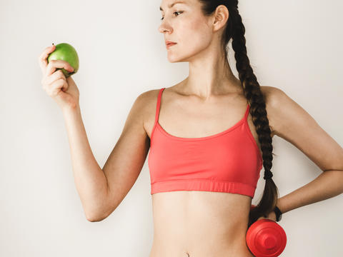 Cute woman with apple during training with dumbbells Photo