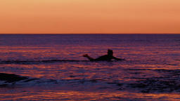 Surfer Paddling Out To Catch A Wave At Sunset Footage