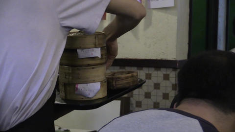 a chinese restaurant waiter putting dim sum to the diners Footage