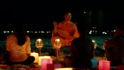 Buddhist Monk Sharing On A Beach At Night Footage