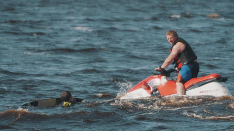 Man in black vest on a jet ski accurately passing by surfer who floats in water Footage