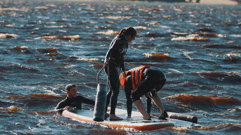 Surfers pushing each other into the water with big soft batons, both falls Footage