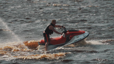 Man in life vest riding on a jet ski on hight speed makes extreme turns Footage