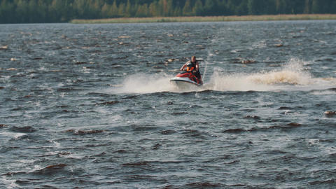 Tracking shot of man and boy in life vest ride a jet ski on hight speed Footage