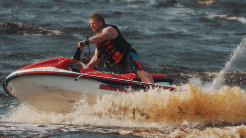Man in life vest showing extreme turns and twists on a jet ski on hight speed Footage