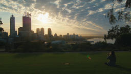 Woman Sitting On The Grass Watching The Sunrise Over Perth City CBD Footage