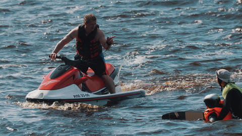 Man on jet ski rides around surfer boy and his coach who floats in water 영상물