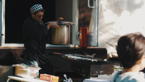 Cooking chef in cap and and black chef jacket put big pot in a brazier outdoors Footage