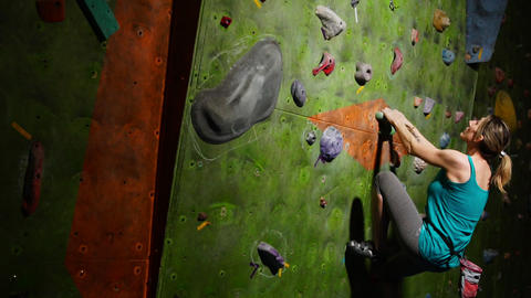 A woman climber is trained to overcome obstacles on the wall for rock climbers Footage