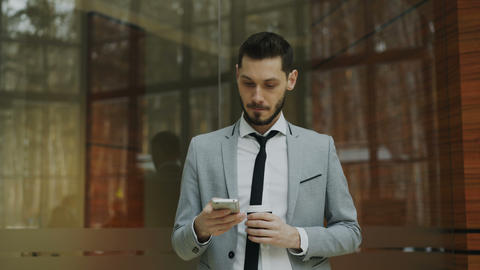 Stedicam shot of businessman talking with smartphone and walking in modern Footage
