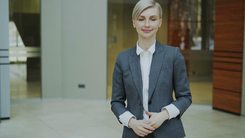 Portrait of successful blonde businesswoman smiling and looking into camera in Footage
