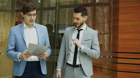 Two businessmen colleagues walking and discussing documents in modern office Footage