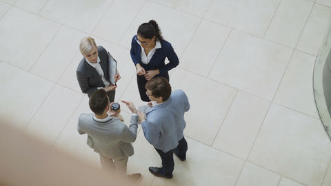Top view of group of business people in suits discussing financial graphs in Live Action