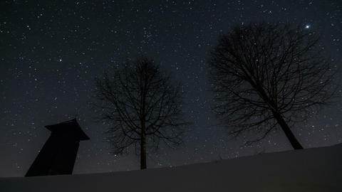 Stars moving in night sky over wooden bell-tower and trees silhouette in winter, Footage
