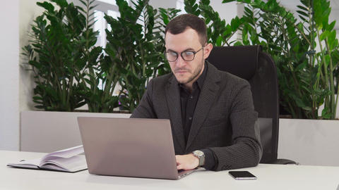 Confident businessman with glasses using a laptop Footage