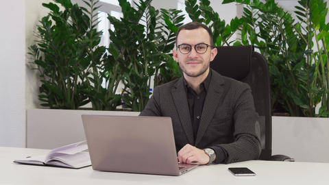 Successful businessman in suit smiling at workplace Live Action