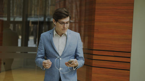 Happy businessman listening music with earphones dancing and walking in lobby of Footage