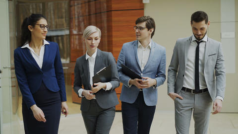 Stedicam shot group of young business people talking and walking in office lobby Footage