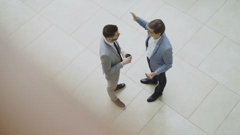 Top view of two businessmen chatting and discussing financial report standing in Footage