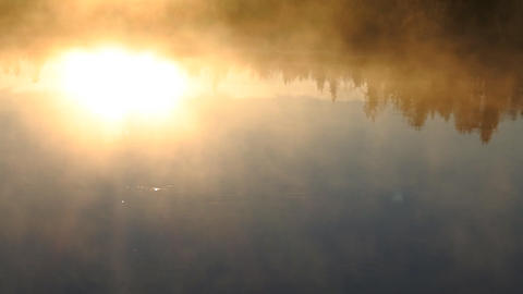 Mist shrouds over river current, rising sun reflected in water Footage