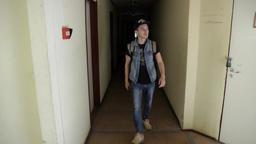 Man in cap backpack walk out dark corridor go down wooden stairs inside building ビデオ