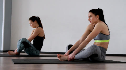 Beautiful girls perform an exercise for posture sitting in a butterfly posture Footage