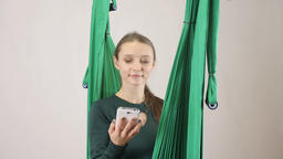 Young woman sits on a hammock and answers a phone call, smartphone. Aerial aero Footage