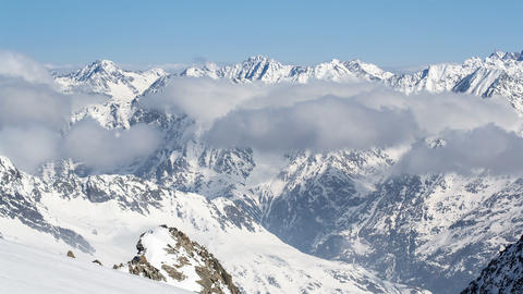 Sunny Day Above Low Clouds in Winter Snowy Alps Mountains Time Lapse Footage