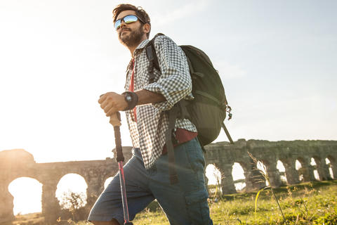 Young attractive man backpacker hiker with sunglasses walking with sticks in フォト