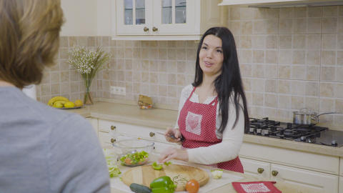 Woman talks with her husband while preparing salad Footage