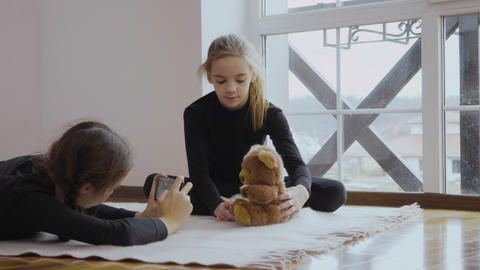 Two girls photographs teddy bear Footage