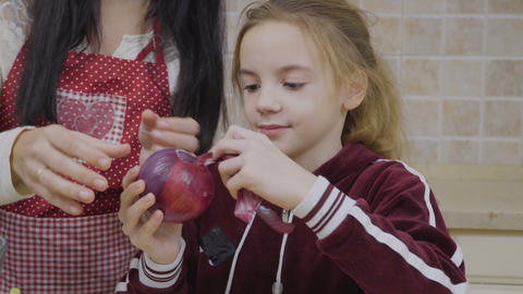 Little girl help mother to peel onion for salad Footage