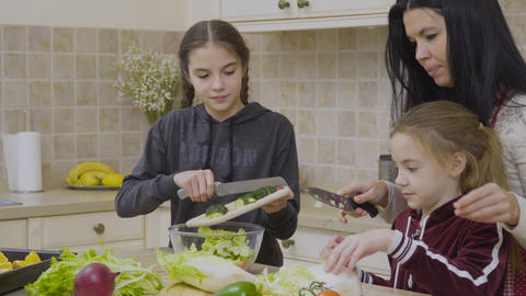 Little girls help mother to cook salad for dinner Footage
