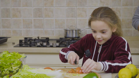 Little girl learns to cut tomato Footage